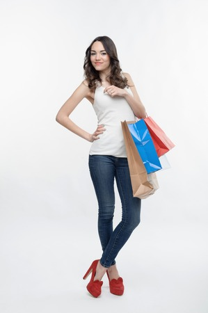 curly headed: Beautiful curly headed smiling girl wearing nice white vest and blue jeans, standing in chic red bootee, holding three packages from the department store  Isolated on the white