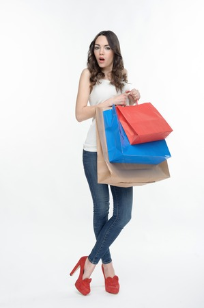 curly headed: Full length portrait of nice curly- headed girl with colorful packages from the mall, thinking that she forgot to buy black dress  Isolated on the white  Stock Photo