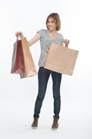 boasting: Full length portrait of pretty fair-haired smiling girl boasting of her purchases  Isolated on the white
