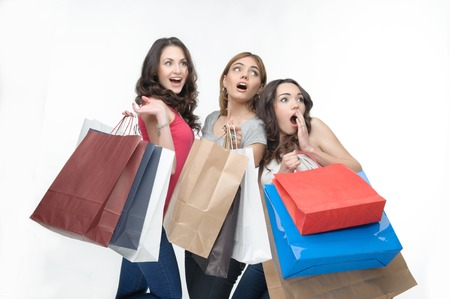selloff: Half-length portrait of three lovely girls with many packages surprised seeing a great sell-off  Isolated on the white