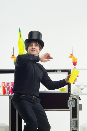 topper: Half-length portrait of handsome barman wearing black topper and holding yellow bottle on his hand