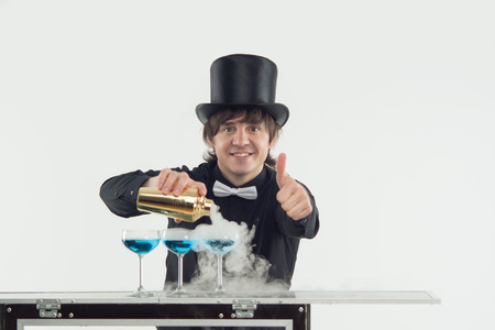 conjuring: Half-length portrait of smiling dark-haired barman wearing nice black topper and shirt conjuring with his tasty blue cocktail