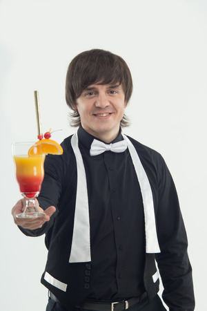 suggested: Half-length portrait of handsome dark-haired smiling barman wearing elegant black shirt and white bow-tie suggested us very delicious orange cocktail  Isolated on the white backgound