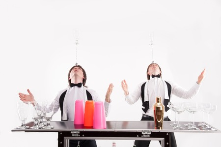 barmen: Two handsome barmen standing near the bar counter with different glasses and shaker on it holding on their head bar spoon with empty glass on the top Stock Photo