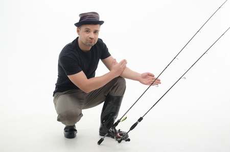 waders: Pescador feliz sentado en grandes botas negras que nos muestra el tama�o de los peces capturados aislados sobre fondo blanco Foto de archivo