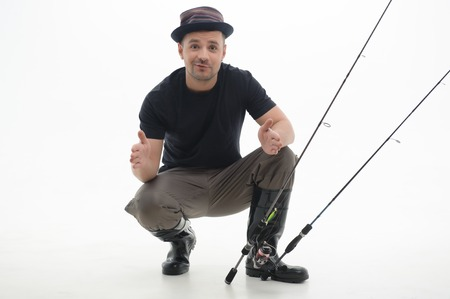 botas altas: Pescador feliz sentado en grandes zancudas negro nos muestra el tamaño de los peces que sorprendida aislados sobre fondo blanco
