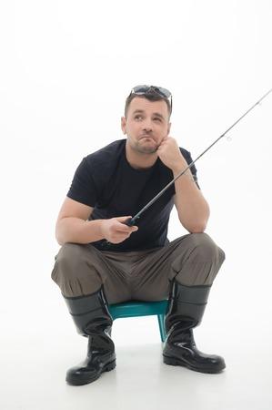 botas altas: Pescador joven sentado y el pensamiento de pescado sobre el más grande capturado había aislado sobre fondo blanco