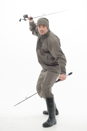 waders: Very strained fisherman wearing grey watertight costume and black waders holding two fishing rods like ninja  Isolated on white background