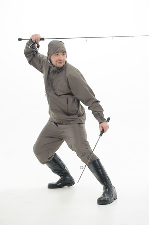 botas altas: Pescador muy tensa vistiendo traje gris y botas a prueba de agua negro la celebración de dos cañas de pescar como ninjas aislado sobre fondo blanco