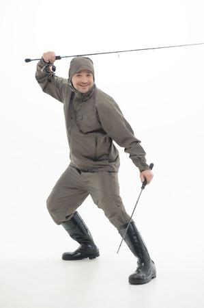 waders: Pescador sonriente vistiendo traje a prueba de agua gris y botas negras de dos varillas de pescadores como ninjas aislado sobre fondo blanco