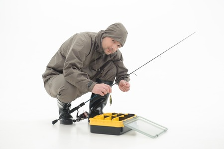 suspiciously: Fisherman sitting in grey watertight costume and stringing bait on the spinner looking at us suspiciously  Isolated on white background