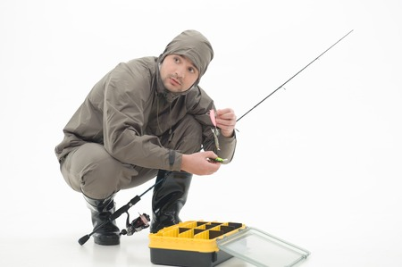 far off: Fisherman holding baits and his fishing rod in his hands sitting near the yellow box and looking in fright at something far off  Isolated on white background Stock Photo