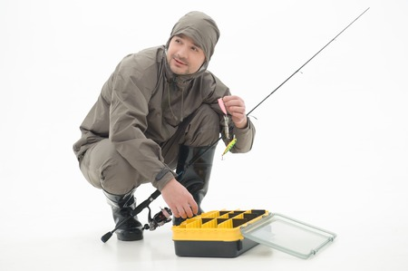 waders: Happy fisherman wearing nice grey watertight costume and black waders sitting near the box with fishing equipment and looking out for his friends  Isolated on white background