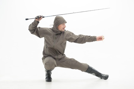 waders: Funny fisherman wearing grey watertight costume and black waders with the spinner posing like ninja  Isolated on white background