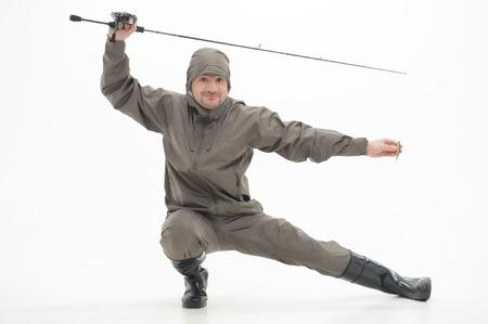 waders: Pescador divertido que desgasta el traje a prueba de agua gris y botas negras con el spinner posando como ninjas aislado sobre fondo blanco
