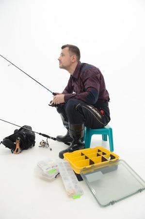 waders: Pescador hermoso que desgasta bonita camisa a cuadros y botas negras que se sientan en la mesa cerca de su equipo y la pesca aislado en el fondo blanco