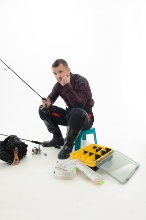 waders: Handsome fisherman wearing nice checked shirt and black waders sitting on the table and thinking about the end of his vocation  Isolated on white background Stock Photo