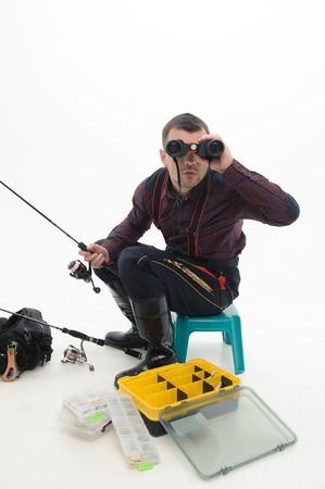 waders: Handsome fisherman wearing nice checked shirt and black waders sitting on the table near his equipment and looking through binoculars  Isolated on white background