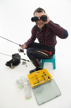 waders: Pescador hermoso que desgasta bonita camisa a cuadros y botas negras que se sientan en la mesa cerca de su equipo y que buscan a trav�s de binoculares aislados en el fondo blanco Foto de archivo
