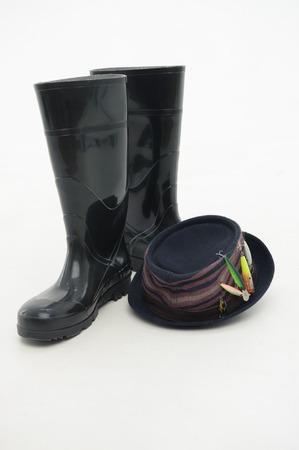 waders: Botas negras a prueba de fallos y sombrero agradable siempre te ayudan durante su pesca aislado sobre fondo blanco