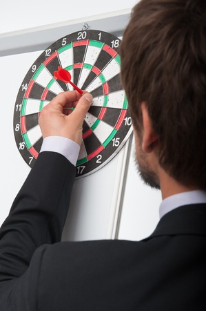 attaching: Portrait of dark-haired bearded man standing back to us attaching dart on target   Stock Photo