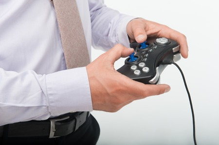joy pad: Man wearing great white shirt and nice tie playing a video game using blue joy pad Stock Photo