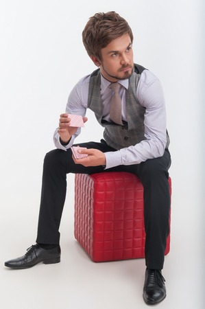 pouffe: Handsome young bearded man wearing nice waistcoat and tie sitting on the red pouffe and shuffling cards  Isolated on white background
