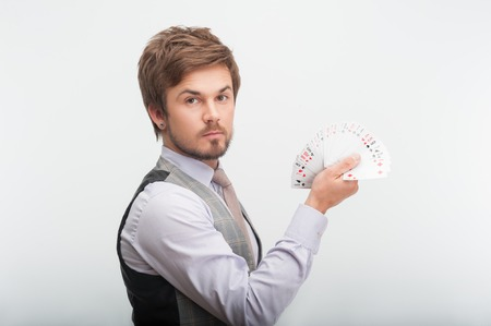 Handsome young man wearing nice grey waistcoat and white shirt showing us all his cards  Isolated on white background photo