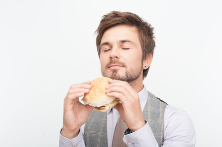 Handsome young man wanted to taste his delicious cheeseburger very much  Isolated on white background Stock Photo