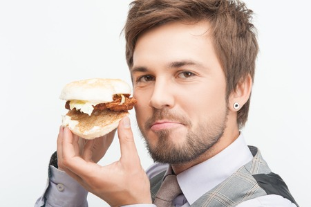 Portrait of handsome young bearded businessman showing us his breakfast lunch and dinner  Isolated on white background photo