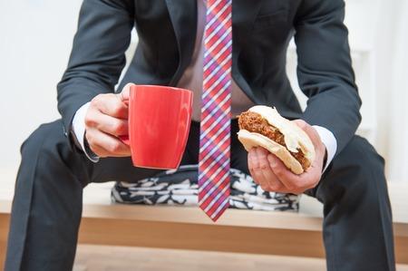 Handsome junge Geschäftsmann mit großen schwarzen Anzug und bunte Krawatte mit einem Snack während seiner Mittagspause im Büro