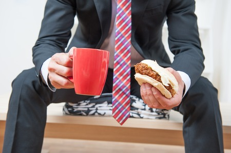 Handsome young businessman wearing great black suit and colorful tie having a snack during his lunch time in the office photo