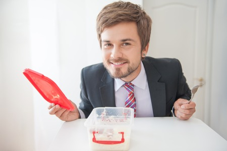 Handsome young smiling businessman opening his box for sandwiches and it is empty photo