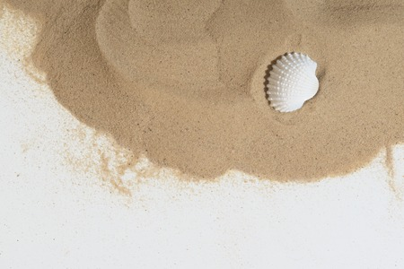 Sand with the sea shell lying on the white sheet for copy place photo