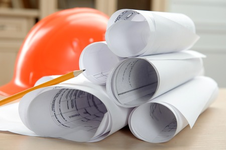 schemes: Orange helmet pen architectonical plans and schemes rolled in a tube lying on the table