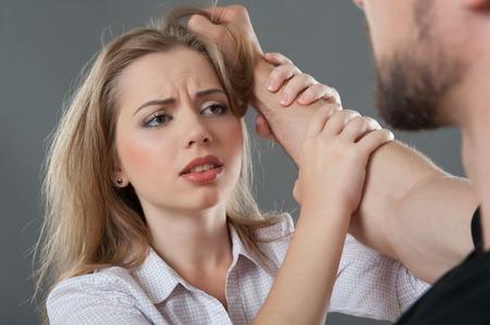 男彼は彼女の髪から分離された灰色の背景上に把握しながら suppliantly 彼を見て彼の手で保持している若い金髪の女性
