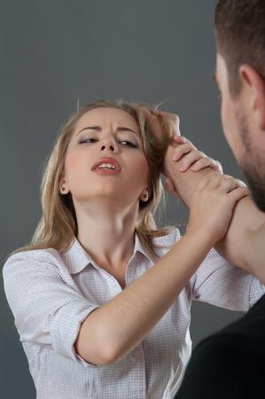 彼は灰色の背景の上で髪分離プロセスを把握しながら suppliantly 彼を見て彼の手で男の保持若い金髪女性