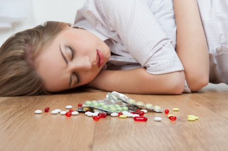Young fair-haired girl in a state of unconsciousness lying on the floor near big heap of different pills   photo
