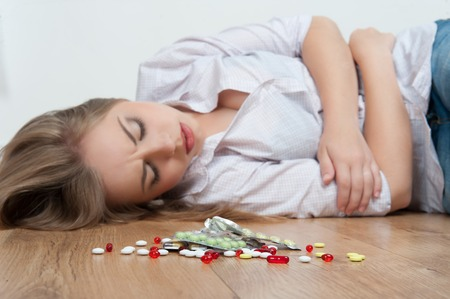 wife beater: Big heap of different pills lying on the floor  Young girl in a state of unconsciousness lying near the pills on background
