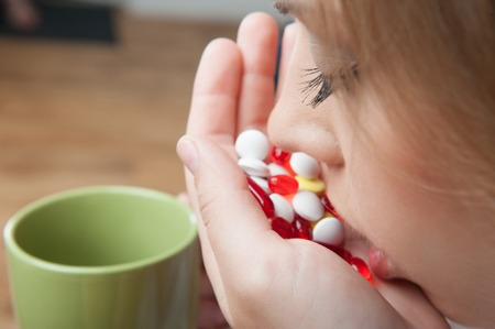 Young girl swallowing bulk of pills  She wants to make away with herself photo