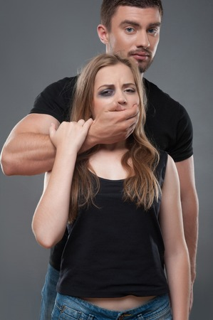 wife beater: Pitiable fair-haired girl having black eye standing with the dark-haired man shut her mouth with his hand  Isolated on grey background Stock Photo