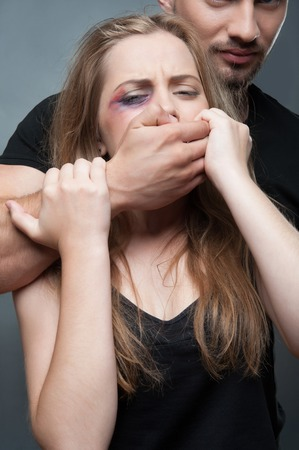heartache: Pitiable fair-haired girl having black eye standing with the dark-haired man shut her mouth with his hand  Isolated on grey background Stock Photo