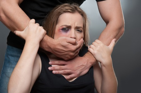 wife beater: Frightened young girl with the black eye wearing black shirt wanted to get free from her heavy-handed husband but she cannot  Isolated on grey background