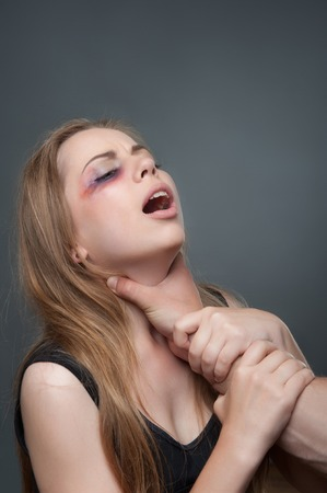 wife beater: Poor young woman with the black eye standing aside to us suffering from the pain  Her husband wants to strangle her  Isolated on grey background Stock Photo