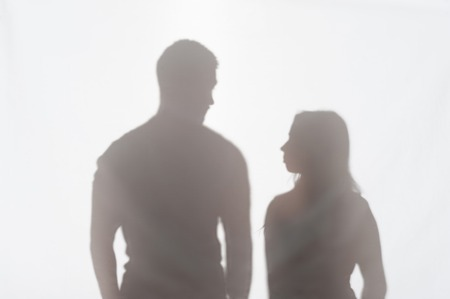 wife beater: Silhouette of man and woman standing on white background and looking at each other