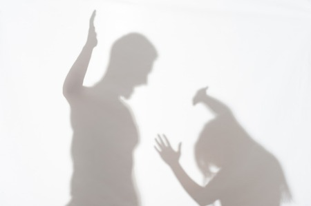 heartache: Silhouette of man striking the woman who cannot to protect herself