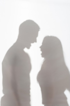 wife beater: Silhouette of man and woman standing on white background and quarrelling