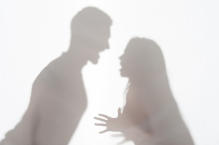 wife beater: Silhouette of man and woman standing on white background and woman wanted to explain something gesticulating with her hands