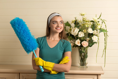 charlady: Pretty smiling dark-haired maid wearing nice blue shirt and jeans standing with the duster near beautiful bouquet of roses and looking at the window