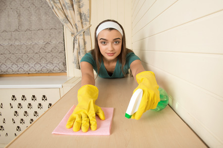 Lovely dark-haired housemaid with the white fillet wearing yellow gloves wiping cream-colored table in the kitchen photo